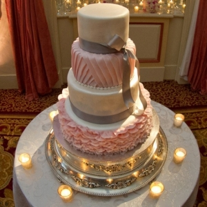 White and pink 4-tier round wedding cake with ruffles, texture and silver ribbon bows