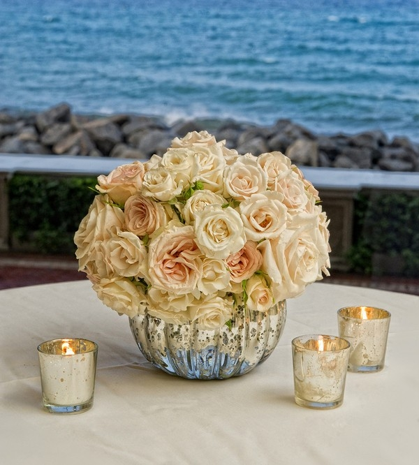 Elegant cream and white rose centerpiece in a mercury glass vase surrounded by mercury glass candles
