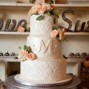 Beautiful lace textured wedding cake with monogram and rose accents on silver stand