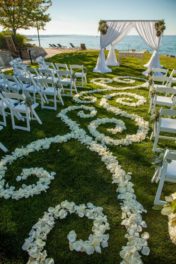 Romantic lakefront ceremony with flower petal designed aisle