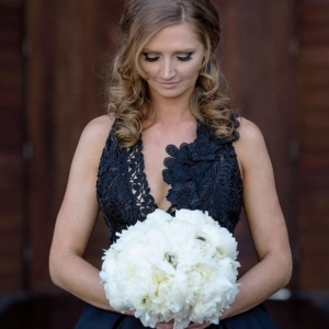 Modern bride wearing black wedding dress and holding bouquet of white peonies