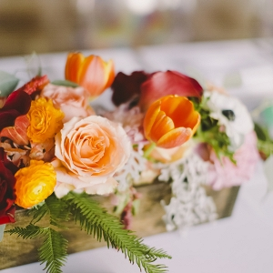 Colorful wedding centerpiece with tulips and roses in a wooden box and tropical green place card