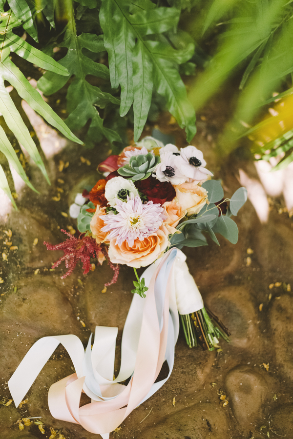 Modern Maui wedding bouquet with dahlias, succulents, roses, anemones, and more tied with pretty pastel ribbons