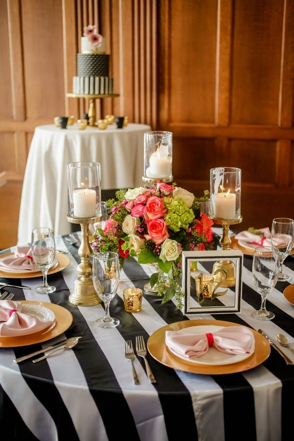 Black and white striped modern tablescape with gold and coral accents