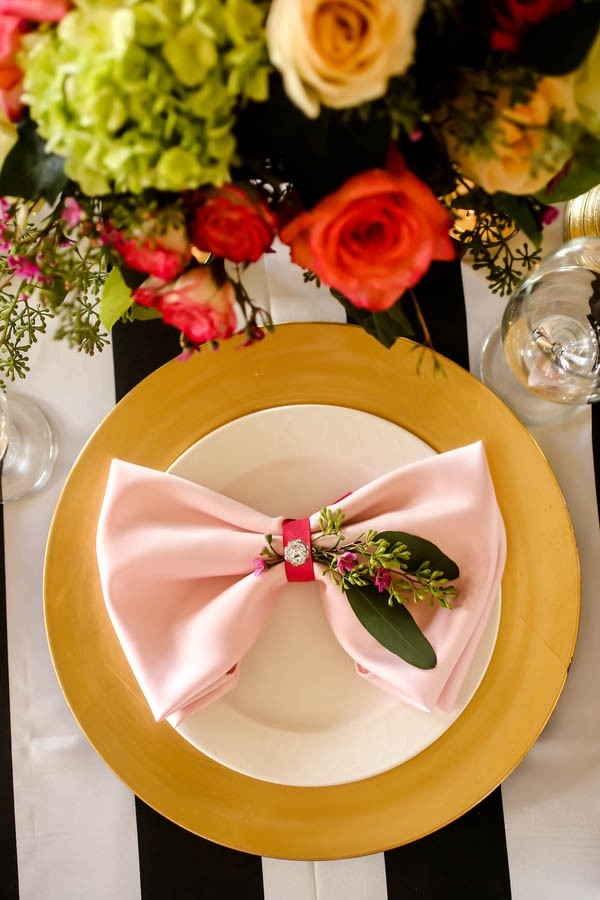 Black, white, gold and pink place setting with bow napkin