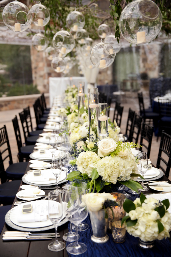Modern wedding tablescape with hanging candles and a dramatic tablescape