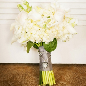 All white wedding bouquet tied with silver ribbon and heirloom locket