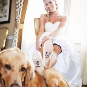"Bride posing with her dog with ""I Do"" shoe decals"