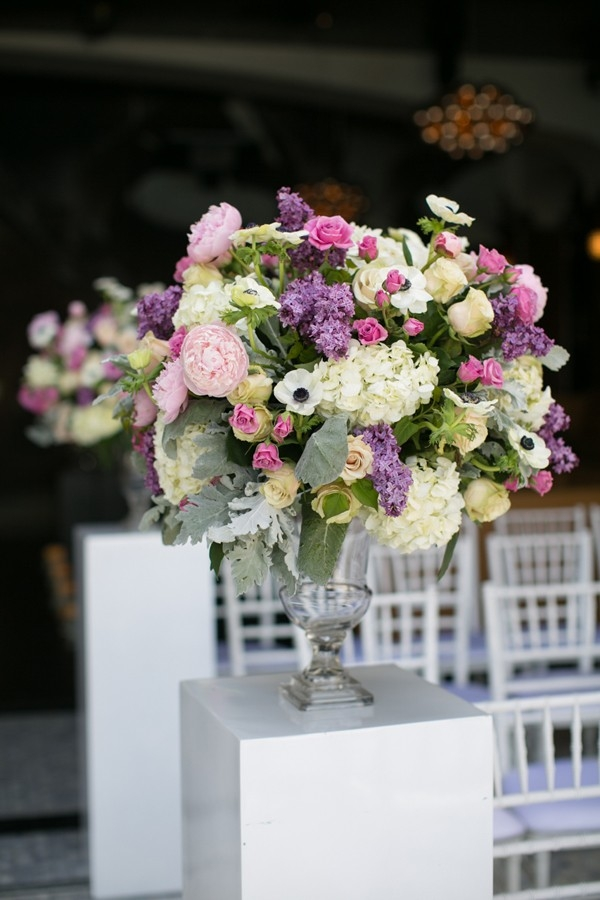 Elegant spring wedding aisle marker made with a variety of flowers in a clear vase