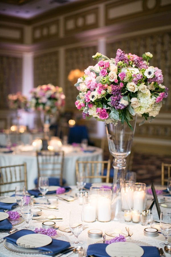 Elegant tall centerpiece with pink and purple flowers, a clear vase and candles
