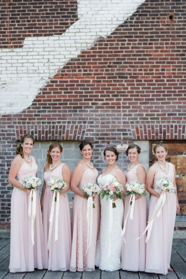Floor length, one shoulder bridesmaid dresses in pink with garden inspired bouquets tied with ribbon