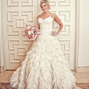 Luxe bride wearing corset wedding dress with feathered skirt, jeweled headband and updo