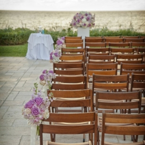 Elegant wedding ceremony overlooking the ocean with wooden chairs and rose bouquet aisle markers