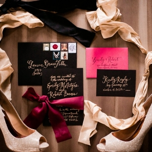 Romantic wedding invitation suite with black envelopes and gold calligraphy and ribbons