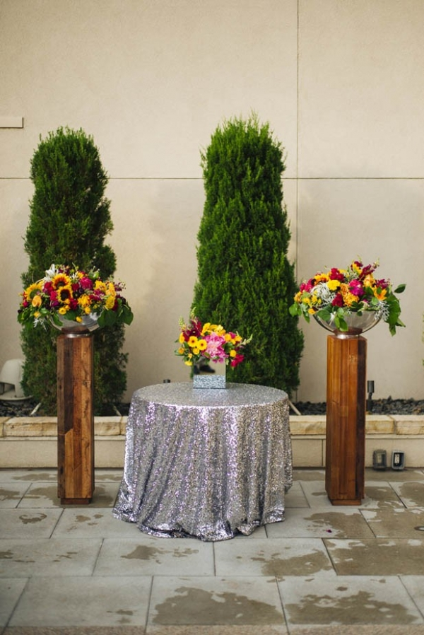 Modern rooftop ceremony with two wooden pillars and a table with a silver glitter tablecloth