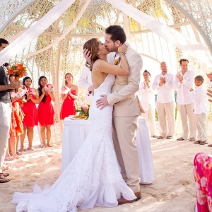 Modern destination wedding bride and groom sharing a kiss under the chic cabana at Sandos Caracol Eco Resort