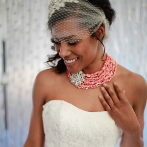 Modern bride with birdcage veil and coral multi-strand necklace