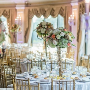 Ballroom reception with elegant tall centerpieces with vines and roses