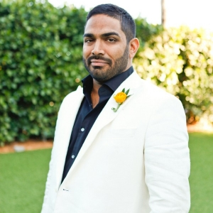 Chic South Beach groom wearing black shirt and white suit with neon orange boutonniere