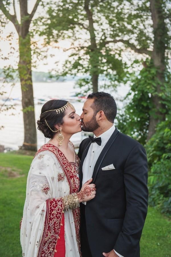 Bride and groom kissing by a lake