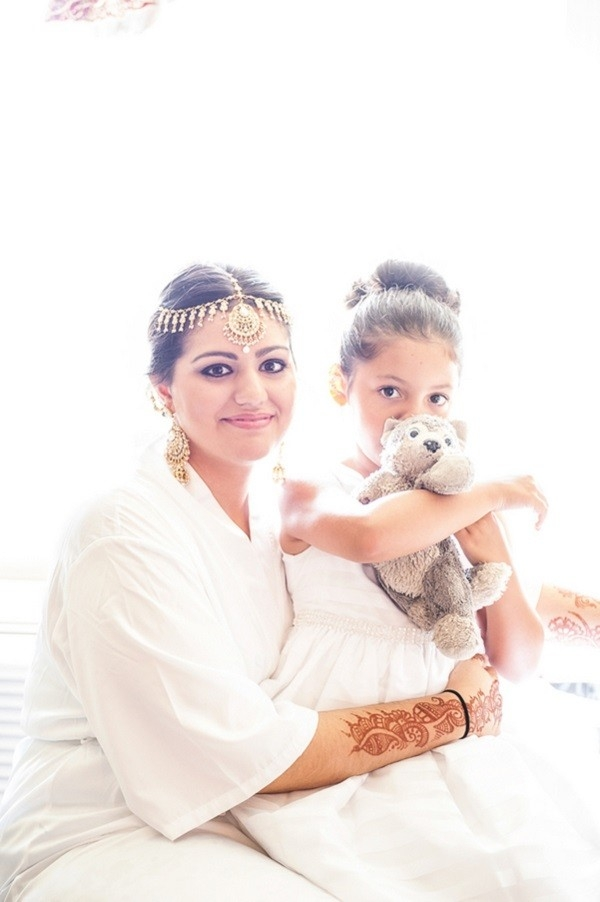 Bride getting ready and holding daughter with stuffed animal