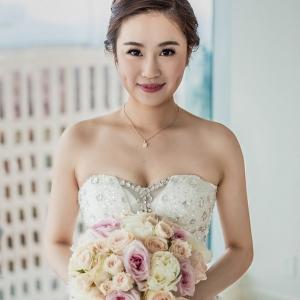 Elegant bride holding classic bouquet of pastel roses