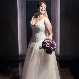 Modern bride wearing deep-v neck Demetrios gown and veil