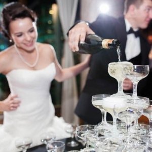Newlywed couple pouring a Champagne tower