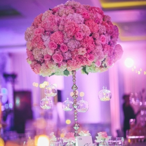 Glamorous tall centerpiece with ombre pink and purple hydrangea and roses and hanging candles