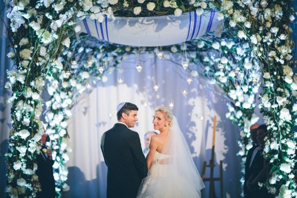 Whimsical floral chuppah with uplighting and hanging candles