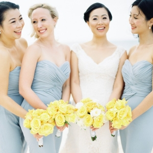 Bridesmaids in gray with yellow rose bouquets