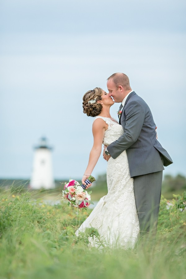 Bride and groom with lighthouse in background