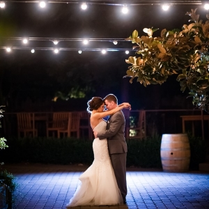 Romantic photo of bride and groom under cafe lights