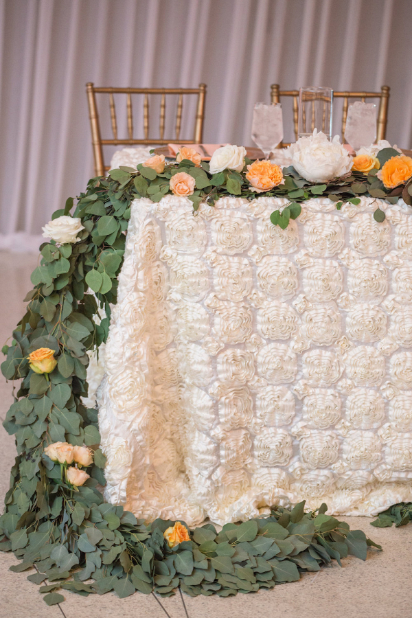 A Sweetheart Table with Centerpiece Garland and Rosette Linen