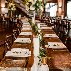 Long farm table wedding reception with greenery runner