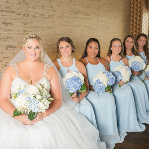 Bridesmaids in light blue dresses with hydrangea bouquets