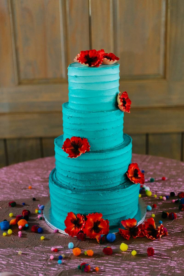 Teal wedding cake with red flowers