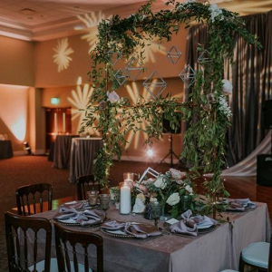 Wedding table with hanging greenery and geometric shapes