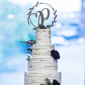 Gold flaked wedding cake with monogram topper