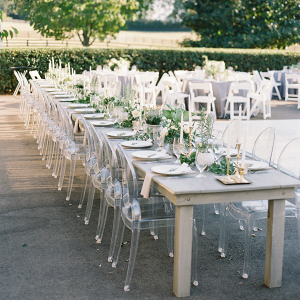 Outdoor wedding reception with farm tables and ghost chairs