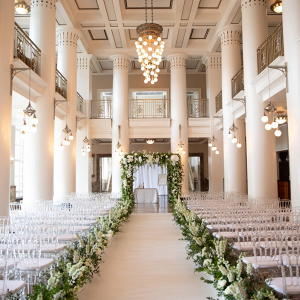 Elegant indoor wedding ceremony with greenery filled aisle and arch