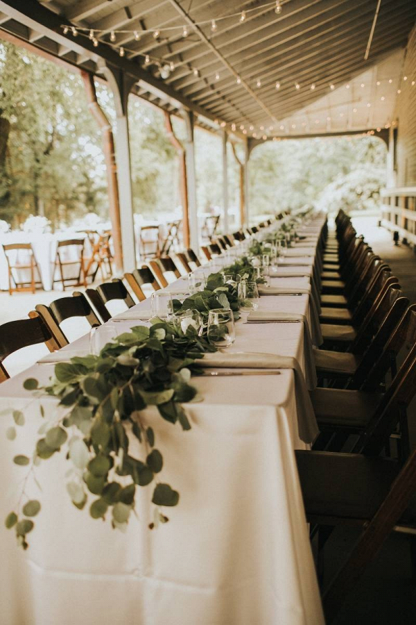 Reception table with long greenery garland runner