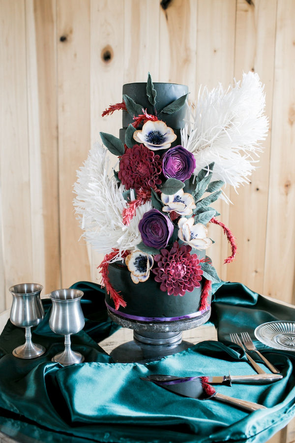 Black wedding cake with feathers and red and purple sugar flowers