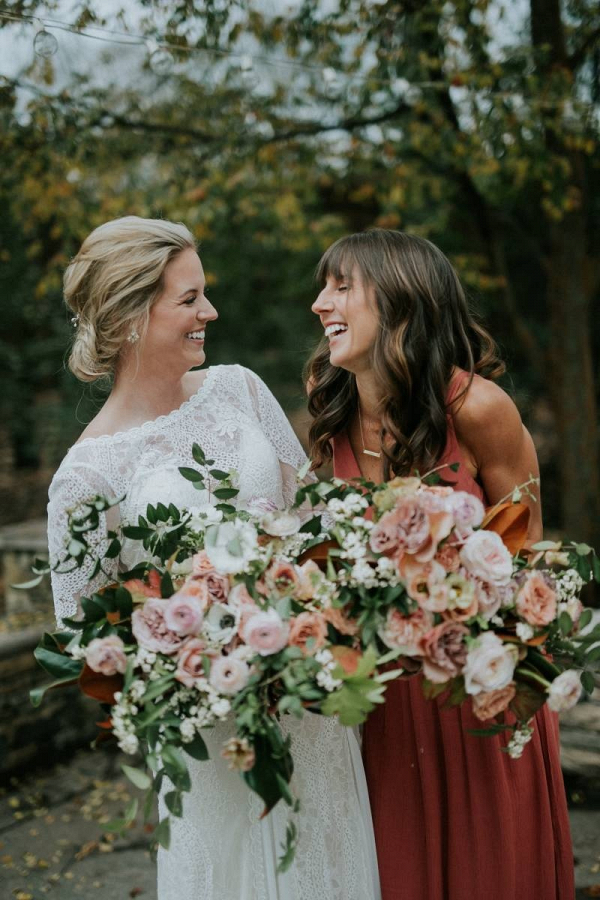 Bride in long sleeve lace gown with bridesmaid in rust dress