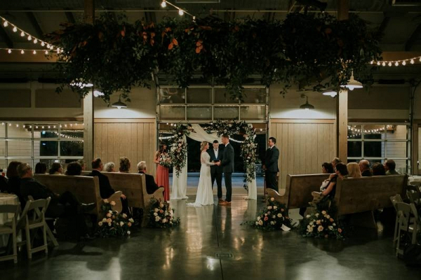 Barn wedding ceremony with hanging greenery and floral arch