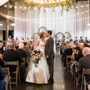 Barn wedding ceremony with draping and floral chandeliers