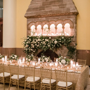 Elegant white wedding reception with floral covered fireplace