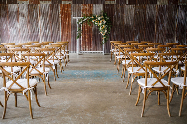 Barn wedding ceremony with arch