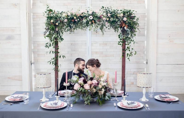 Sweetheart table with floral wedding arch