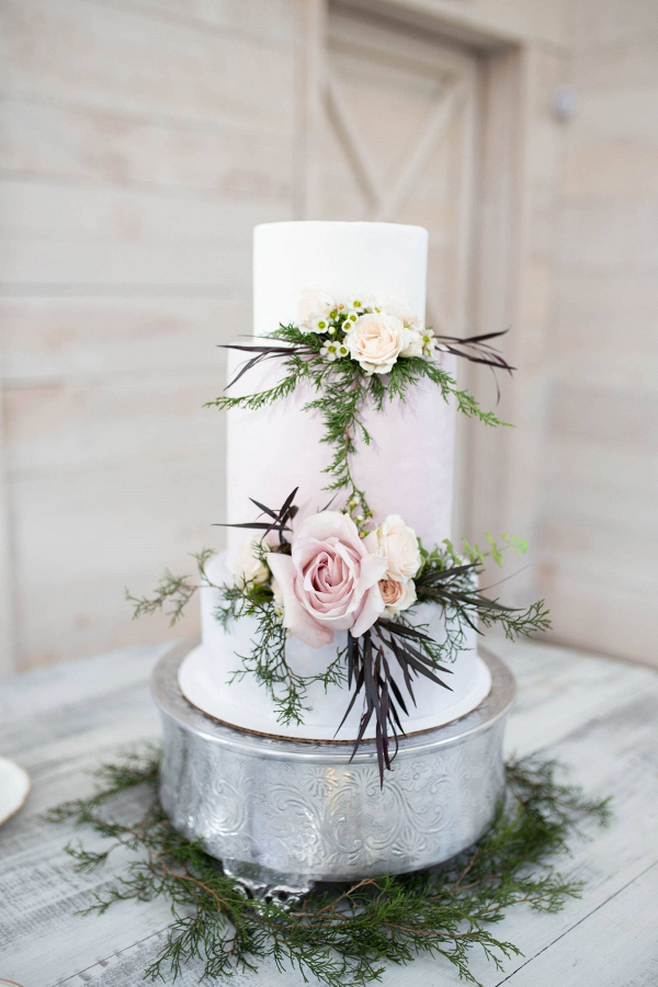 Tall white wedding cake with fresh flowers